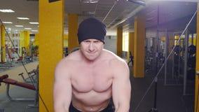 El hombre entrena al bíceps en el gimnasio