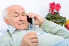El hombre envejecido cansado desanimado llama a sus parientes imagen de archivo