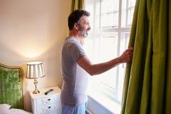 El hombre envejecido centro abre las cortinas en la habitación por la mañana Imagen de archivo libre de regalías