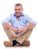 El hombre envejecido centro casual se sienta y sonríe Imagen de archivo libre de regalías