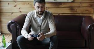 El hombre envejecido centro con una barba está sosteniendo un control remoto y está jugando a un videojuego almacen de video