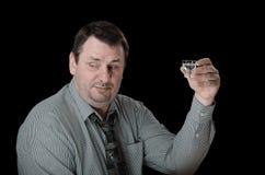 El hombre envejecido centro sostiene el tiro de la vodka Fotografía de archivo libre de regalías