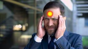 El hombre envejecido centro sufre del dolor de cabeza, punto indica el dolor de la jaqueca, primer imagen de archivo libre de regalías