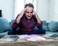 El hombre envejecido medio trastornado subrayó sobre deudas de la tarjeta de crédito y finanzas que consideraban no felices de lo fotografía de archivo libre de regalías