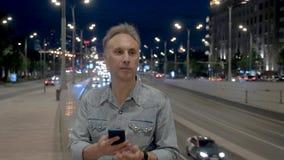 El hombre envejecido medio utiliza smartphone en el parapeto en la igualación de la ciudad almacen de metraje de vídeo