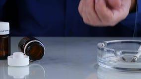 El hombre enviciado con comportamiento vicioso toma píldoras con alcohol y fuma un cigarrillo metrajes