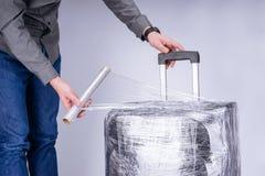 El hombre envuelve la película protectora de la maleta fotos de archivo libres de regalías