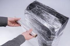 El hombre envuelve la película protectora de la maleta fotografía de archivo