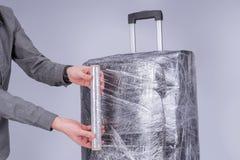 El hombre envuelve la película protectora de la maleta imagen de archivo
