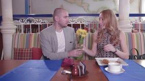 El hombre es atrasado para la fecha y una mujer es ceño fruncido, ella da una bofetada con las flores almacen de video