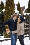 El hombre es caja de las pieles detrás el suyo parte posterior y yendo a dar a su mujer un presente en día del ` s de la tarjeta  foto de archivo