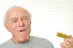 El hombre es feliz comiendo el apio y la manteca de cacahuete Fotografía de archivo libre de regalías