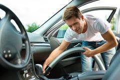 El hombre es hoovering o de limpieza del coche Fotografía de archivo