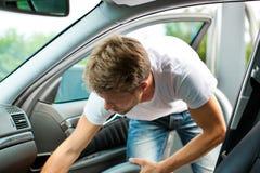 El hombre es hoovering o de limpieza del coche Foto de archivo libre de regalías