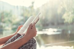 El hombre es libro de lectura en parque hermoso se relaja y ambiente pacífico imagen de archivo