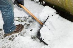 El hombre es nieve que traspala una trayectoria Imagen de archivo libre de regalías