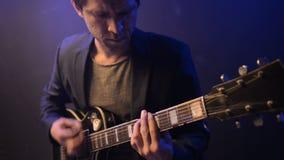 El hombre es que sienta y que toca la guitarra en un cuarto oscuro almacen de video