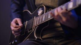 El hombre es que sienta y que toca la guitarra en un cuarto oscuro almacen de metraje de vídeo