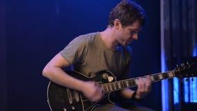 El hombre es que sienta y que toca la guitarra en un cuarto oscuro metrajes