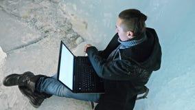 El hombre es se sienta en Internet en ordenador portátil en una cueva de hielo Alrededor de la gruta hermosa misteriosa del hielo almacen de metraje de vídeo