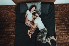 El hombre es vientre que escucha de la mujer embarazada en cama foto de archivo libre de regalías