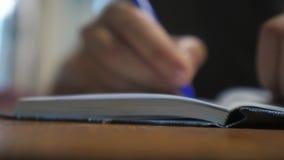 El hombre escribe en cuaderno escritura de la forma de vida de la mano del hombre en una libreta educación del negocio del concep almacen de metraje de vídeo