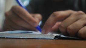 El hombre escribe en cuaderno escritura de la mano del hombre en una libreta educación del negocio del concepto el hombre hace fo almacen de video