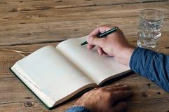 El hombre escribe en un primer en blanco del cuaderno Fotos de archivo