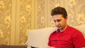 El hombre escucha la música con los auriculares almacen de video