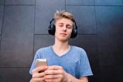 El hombre escucha la música en sus auriculares con sus ojos cerrados, y él lleva a cabo su mano en el fondo de una pared gris imagen de archivo