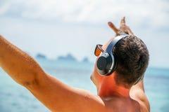 El hombre escucha música en auriculares en la playa imagen de archivo