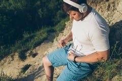 El hombre escucha música en el pico de la colina Imagen de archivo libre de regalías