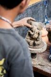 El hombre esculpe el elefante de la arcilla Foto de archivo libre de regalías