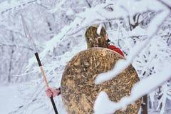 El hombre espartano tomó la cubierta bajo ramas nevosas Foto de archivo