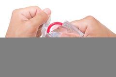 El hombre está abriendo un preservativo, aislado en blanco fotos de archivo