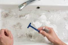 El hombre está afeitando, vista de las manos con una maquinilla de afeitar y el lavabo con agua sucia imagenes de archivo
