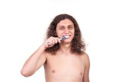 El hombre está aplicando sus dientes con brocha fotos de archivo