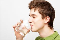 El hombre está bebiendo el agua mineral Imagenes de archivo
