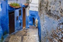 El hombre está caminando abajo de la calle en la lluvia en la ciudad azul Fotografía de archivo