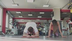El hombre está cansado después del entrenamiento individual con el coche femenino en gimnasio Individuo obeso grueso con el instr almacen de metraje de vídeo