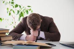 El hombre está cansado y dormido en una tabla en una oficina de negocios imagenes de archivo