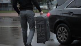 El hombre está cargando la maleta grande con la manija en el tronco del coche almacen de metraje de vídeo
