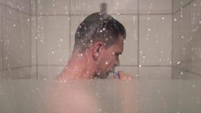 El hombre está cepillando sus dientes en la ducha almacen de metraje de vídeo