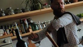 El hombre está cocinando y está bailando Inconformista masculino carismático en cocina almacen de metraje de vídeo