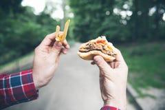 El hombre está comiendo en el parque y está gozando de la comida deliciosa Imagen de archivo