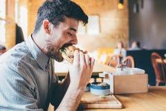 El hombre está comiendo en un restaurante y está gozando de la comida deliciosa Foto de archivo libre de regalías