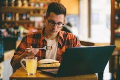 El hombre está comiendo en un restaurante y está gozando de la comida deliciosa Fotografía de archivo libre de regalías