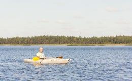 El hombre está conduciendo el kajak en agua Imagen de archivo libre de regalías