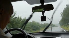 El hombre está conduciendo en el camino más allá del bosque metrajes