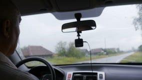 El hombre está conduciendo en coche a través del pueblo almacen de metraje de vídeo